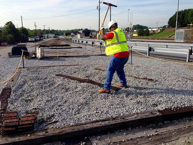 A Railinc employee drives a rail spike in the yard at CSX REDI.